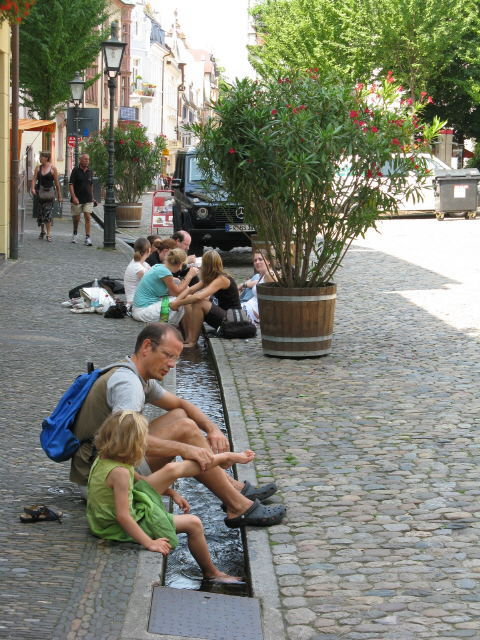 People sitting (but not drinking) near the wonderful Bächle that flow through the city of Freiburg.